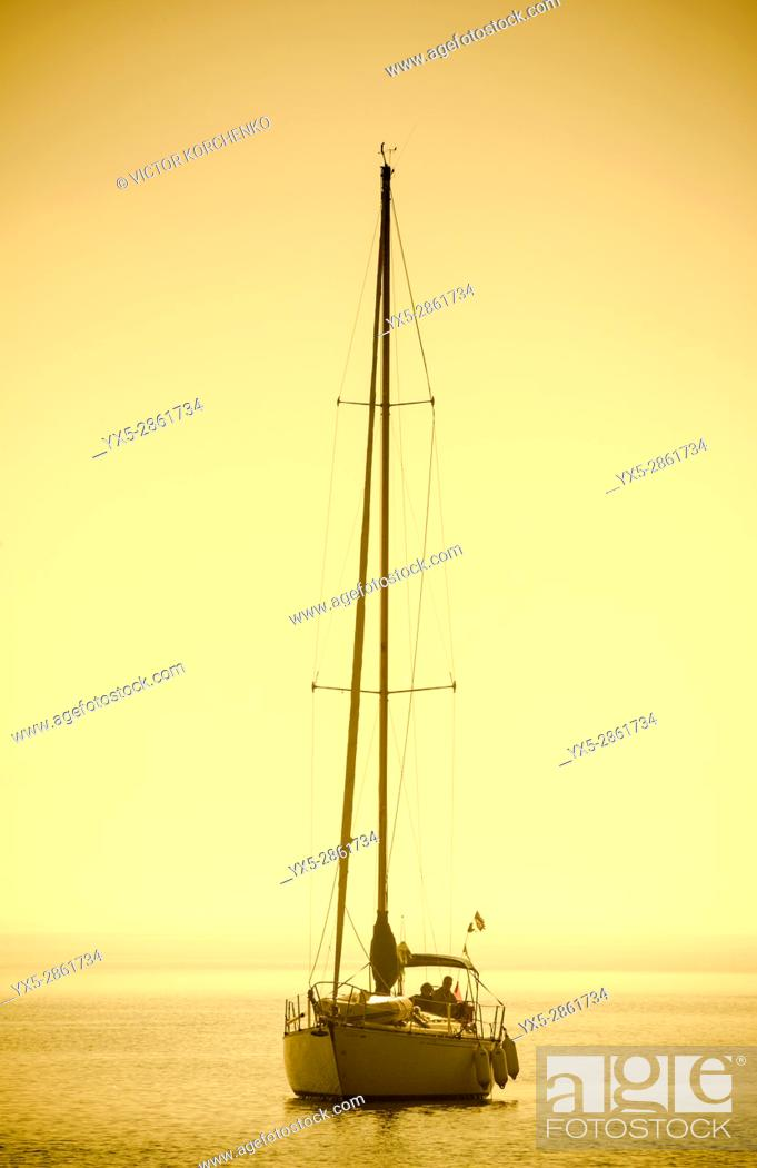 Imagen: Yacht with sails down entering Oakville marina on lake Ontario.