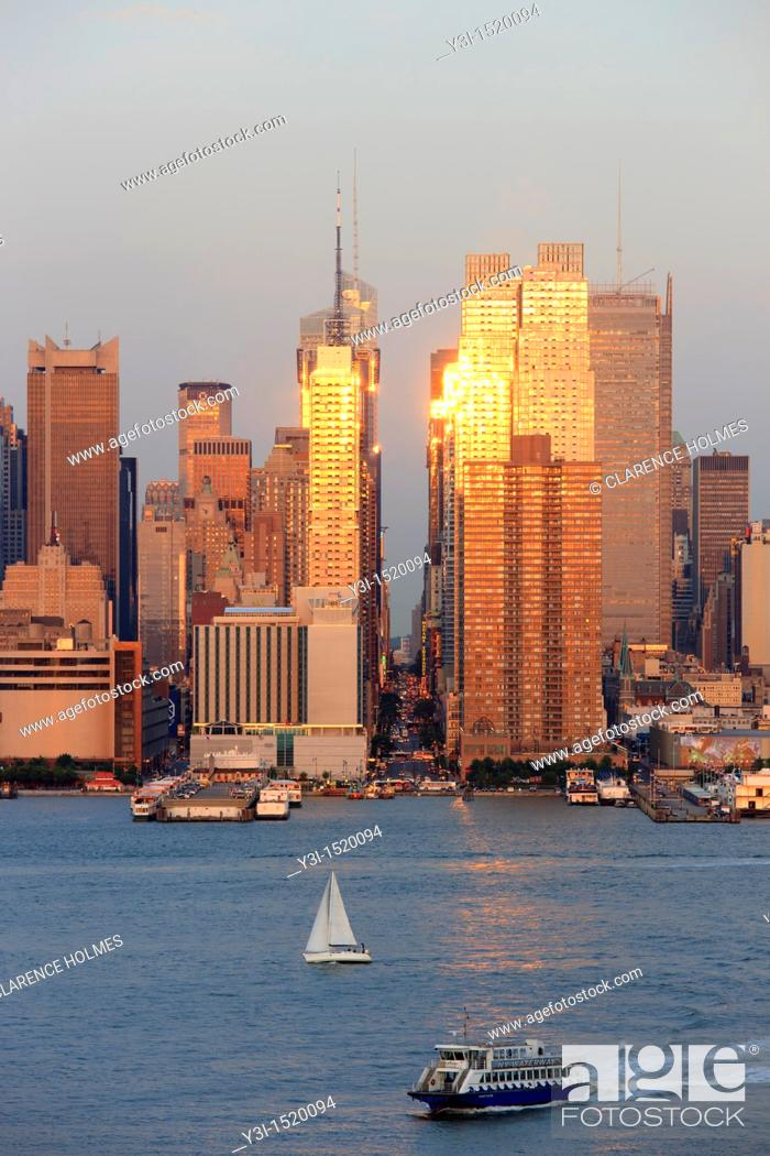 Stock Photo: The setting sun reflects off the windows of Manhattan skyscrapers on 42nd street in New York City, New York, USA as viewed over the Hudson River from New Jersey.