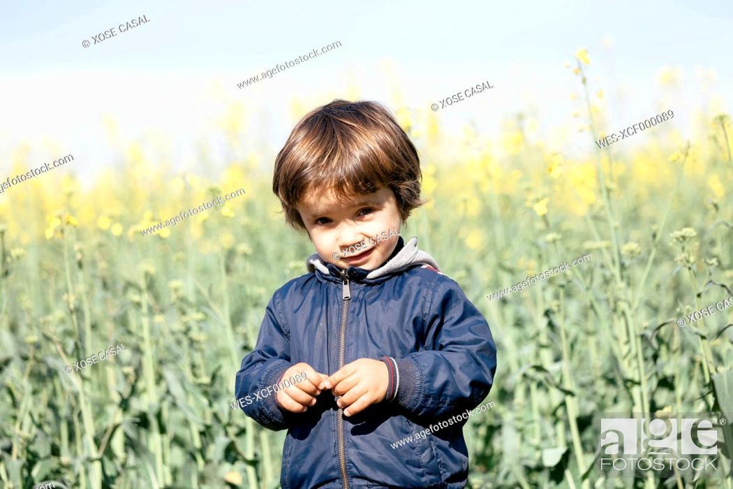 Stock Photo: Portrait of little boy standing in front of rape field.