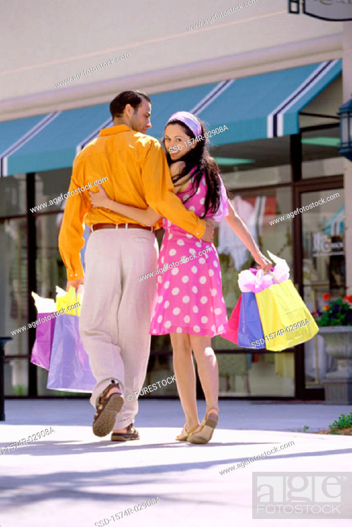 Stock Photo: Rear view of a young couple walking with shopping bags.
