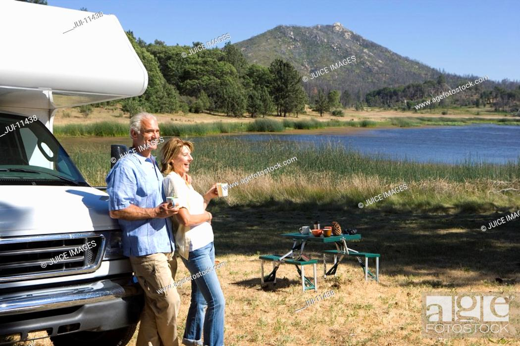 Stock Photo: Mature couple with mugs by motor home by lake, side view.