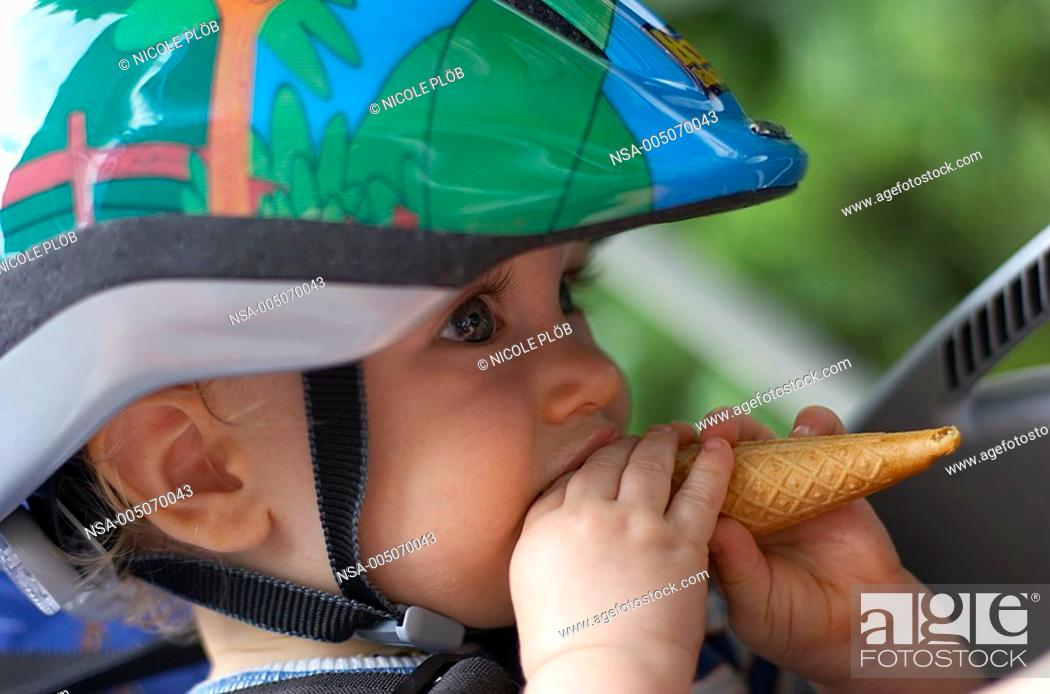 Stock Photo: baby with helmet and ice-cream cone in child seat.