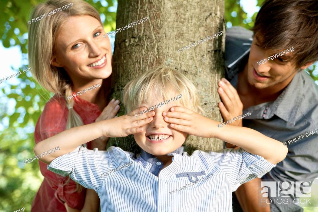 Stock Photo: Germany, Cologne, Boy playing hide and seek with parents.