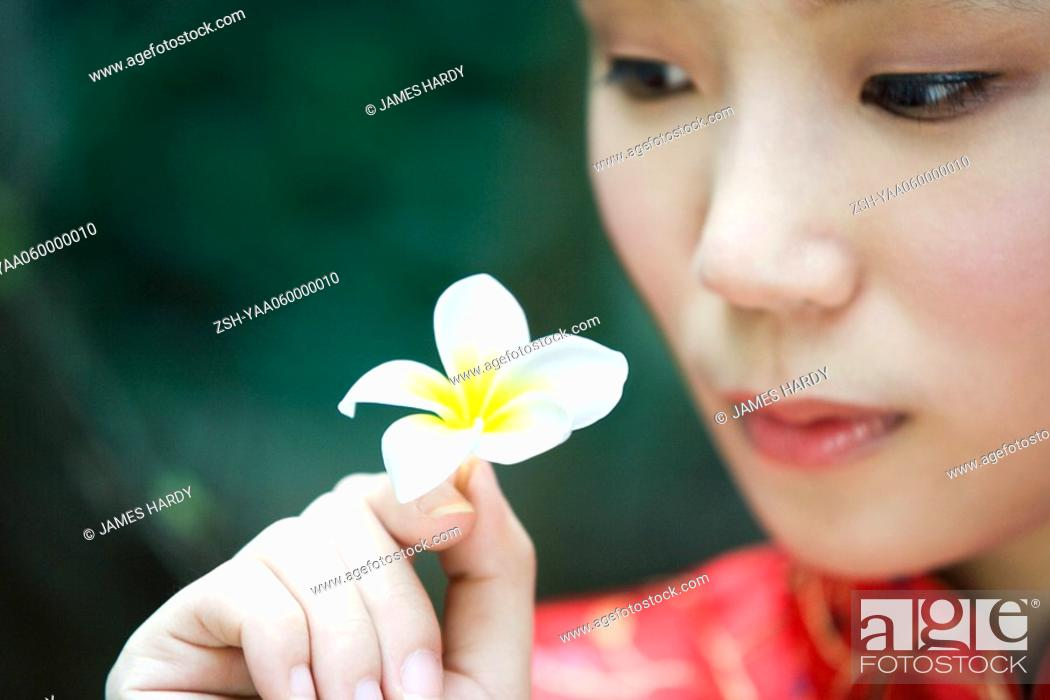 Stock Photo: Young woman dressed in traditional Chinese clothing, holding up flower, close-up.