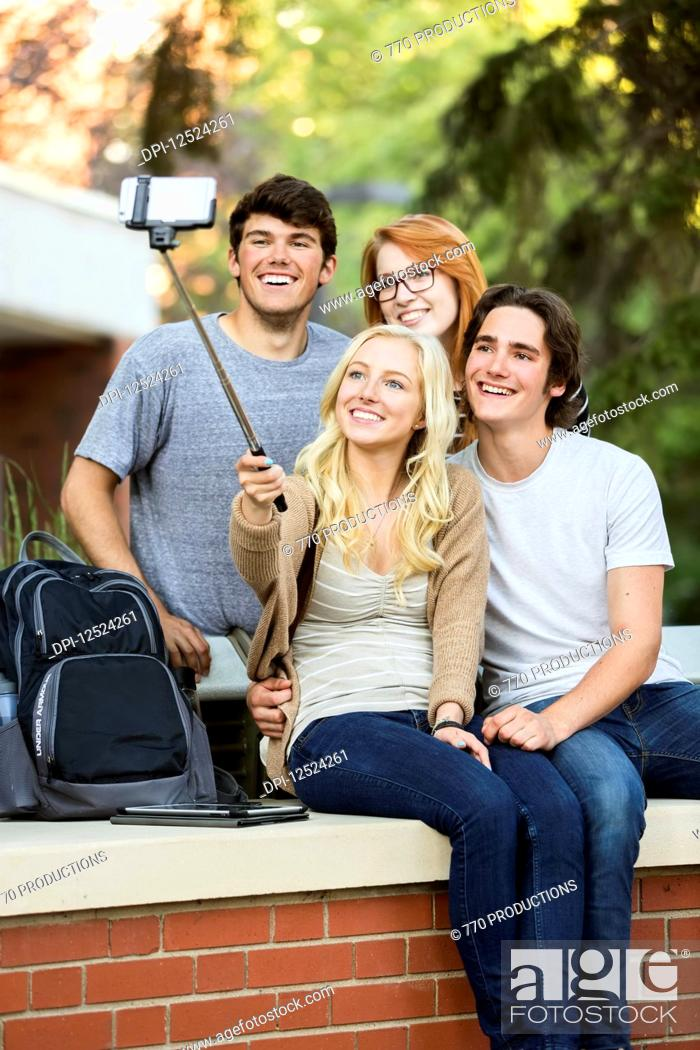 Imagen: A group of four friends sitting on a bench taking a self-portrait with a smart phone using a selfie stick on a university campus; Edmonton, Alberta, Canada.