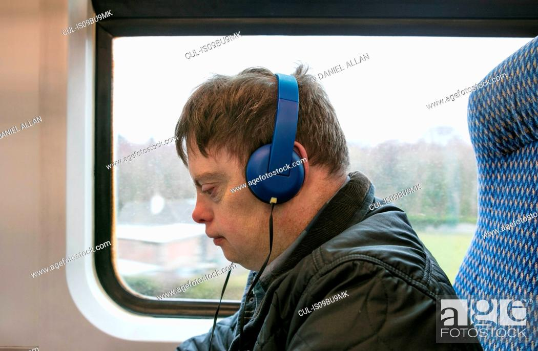 Stock Photo: Man with down syndrome using headphones on train.