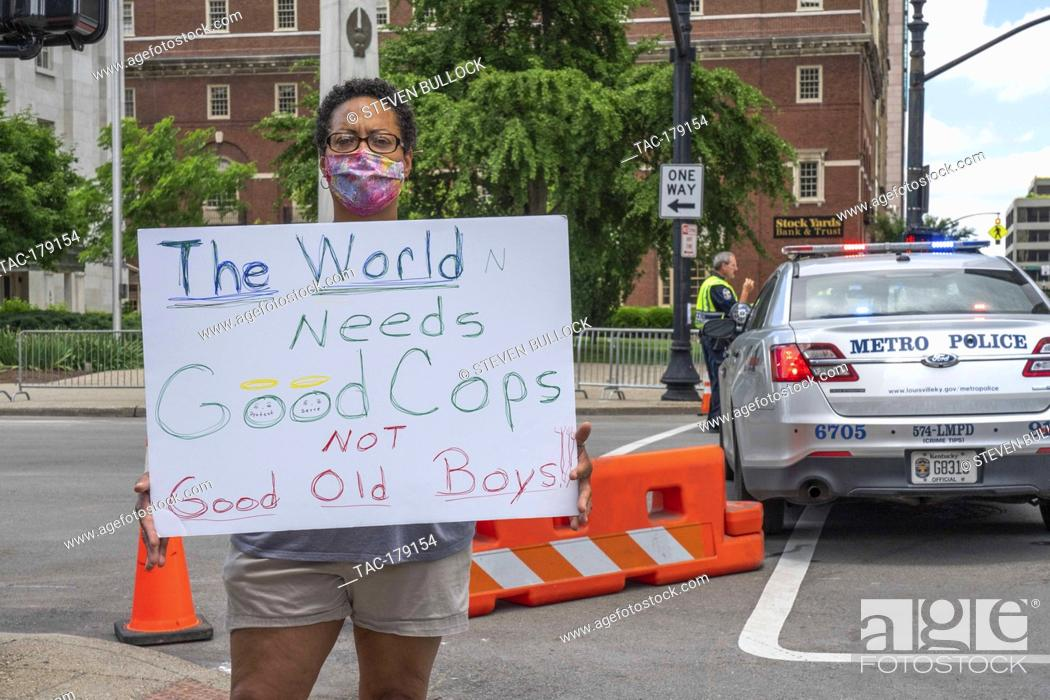 """Stock Photo: Peaceful protester holds signage """"""""The World Needs Good Cops Not Good Old Boys!"""""""" at the area of Friday night's rioting on 4th and Jefferson Street on May 30."""