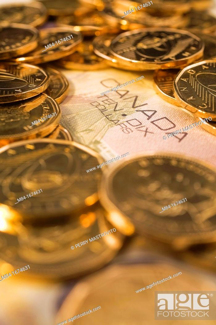 Canadian One Dollar Coins on top of a Ten Dollar Bill, Studio