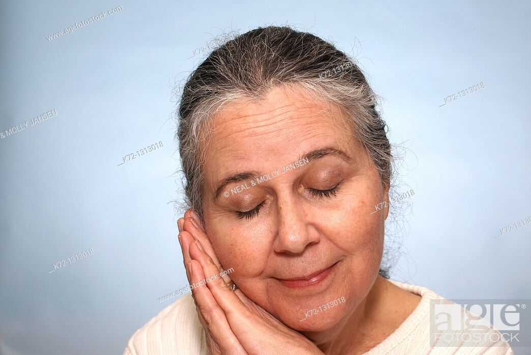 Stock Photo: Portrait of an older woman smiling and resting with eyes closed.