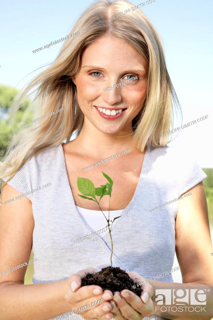 Stock Photo: Germany, Cologne, Young woman holding seedling, smiling, portrait.