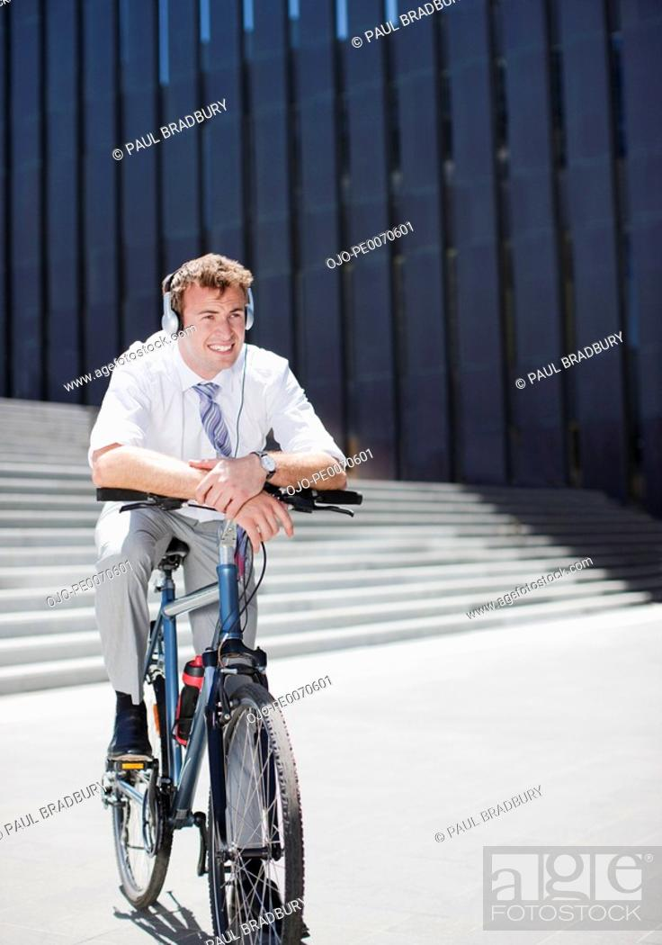 Stock Photo: Businessman in headphones sitting on bicycle.