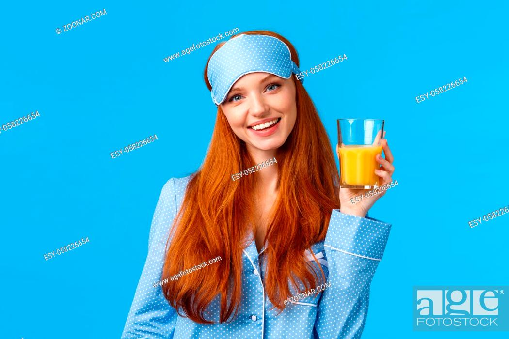 Stock Photo: Daily routine, morning and healthy lifestyle concept. Attractive energized redhead female in nightwear, sleep mask raising glass of juice and smiling satisfied.