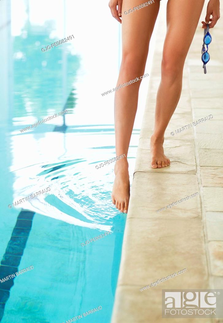 Stock Photo: Woman dipping toe in swimming pool.