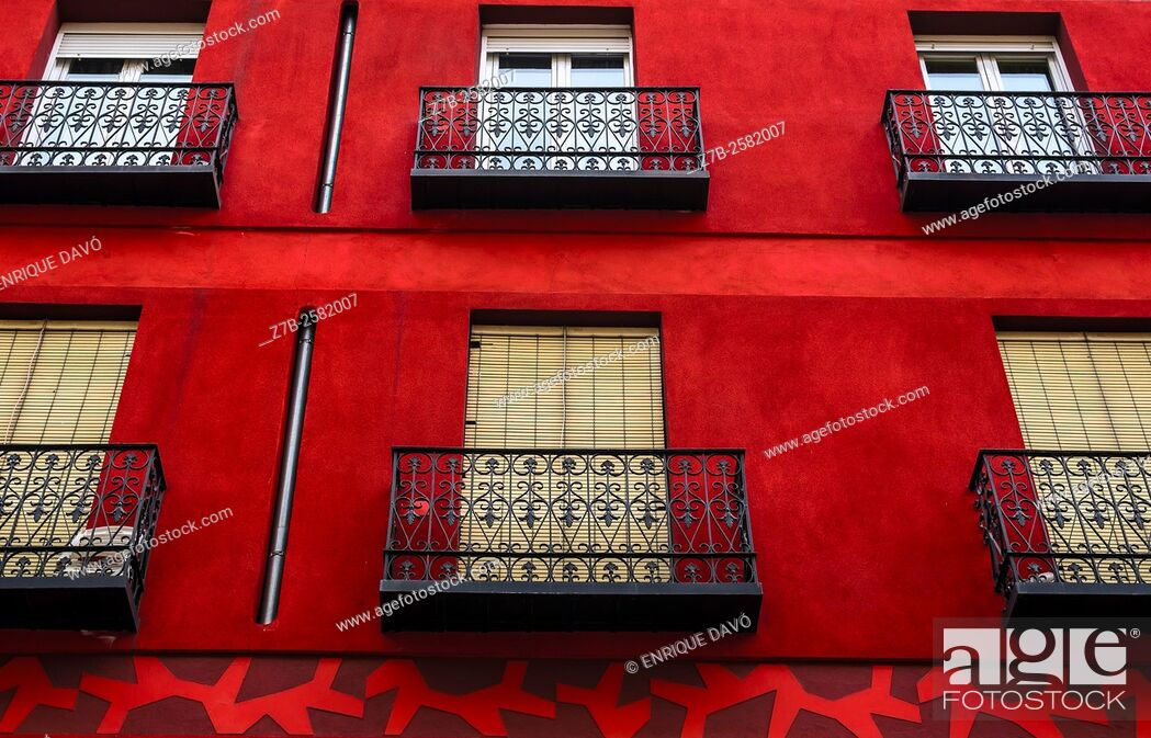 Stock Photo: A red front of a building in a central street of Madrid city, Spain.