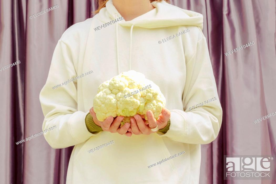 Stock Photo: Close-up of mid adult woman holding cauliflower while standing against curtain at home.