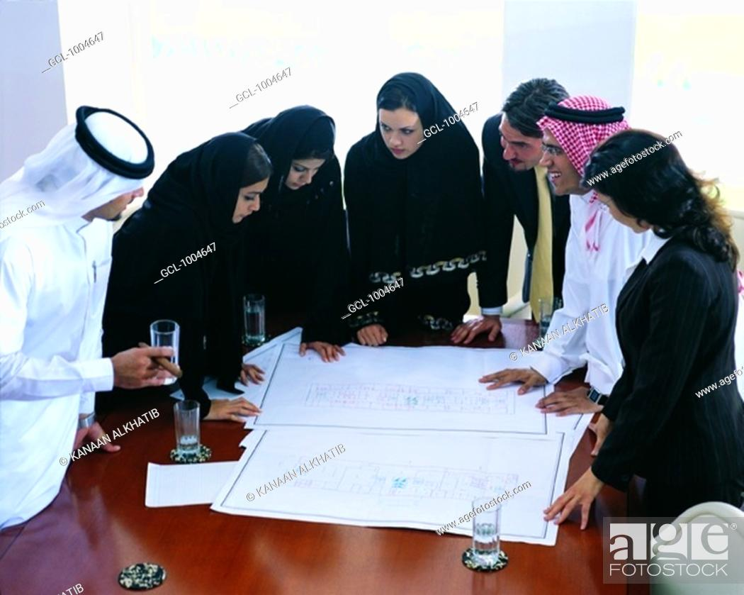 Stock Photo: Arab businesspeople looking at architectural sketches.