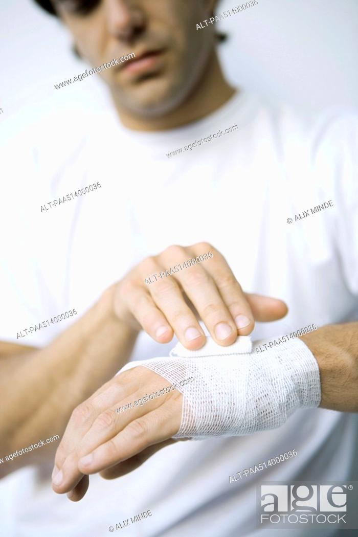 Stock Photo: Man wrapping gauze around his wrist and hand, cropped view.