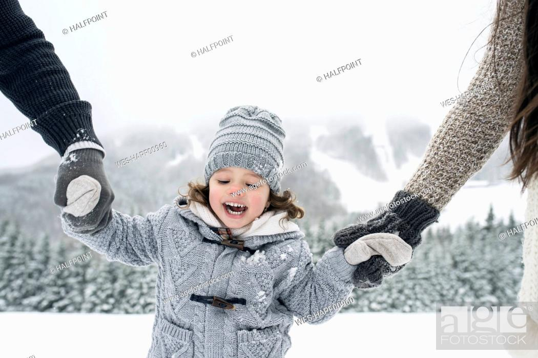 Stock Photo: Happy girl hand in hand with parents in winter landscape.