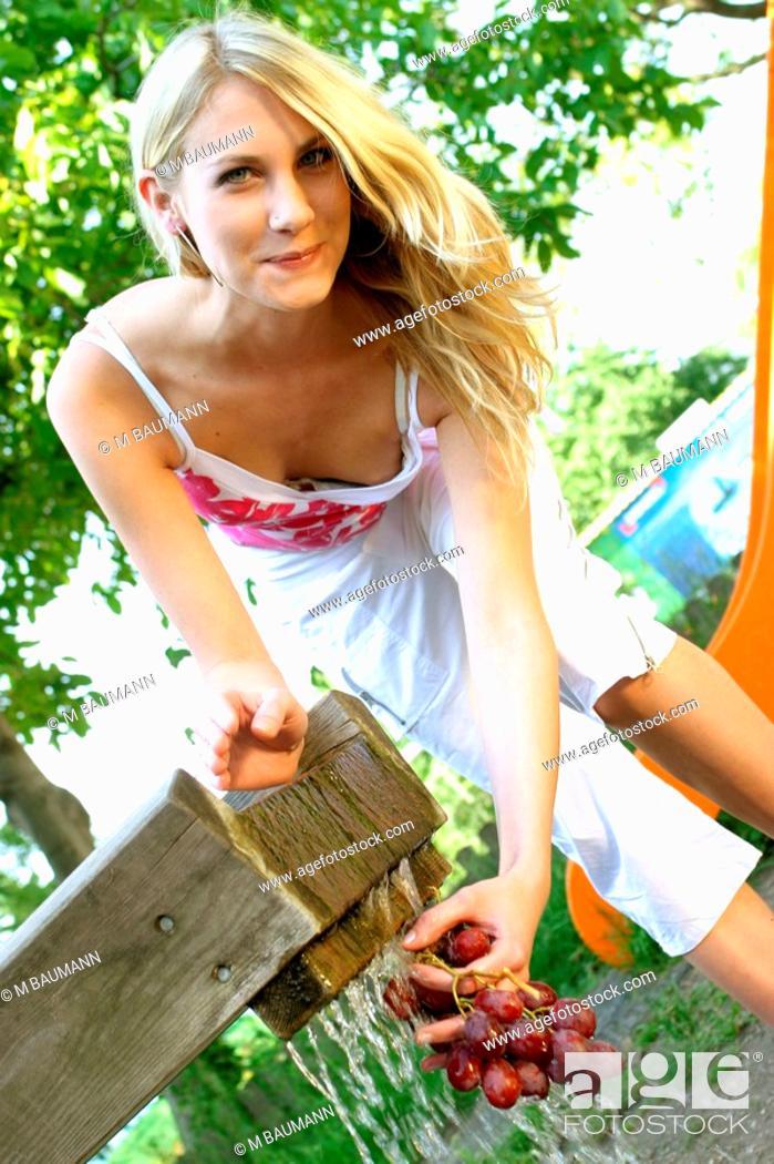 Stock Photo: blond woman washing grapes.