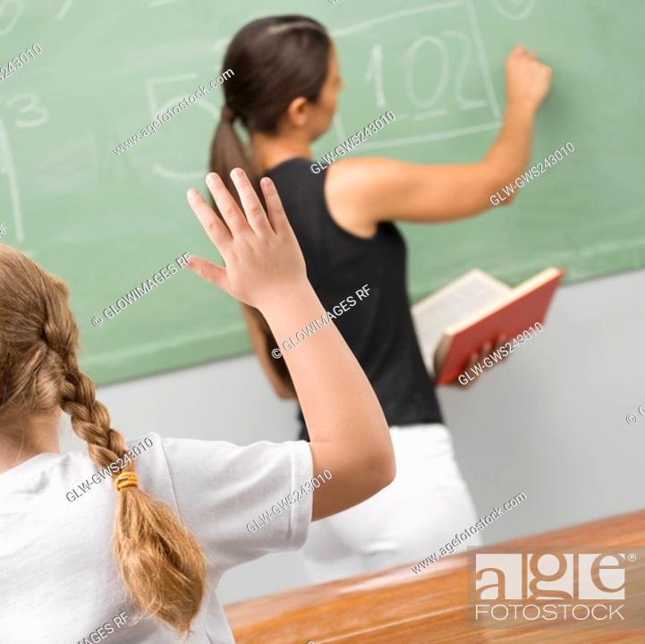 Stock Photo: Rear view of a schoolgirl in a classroom with her hand raised.