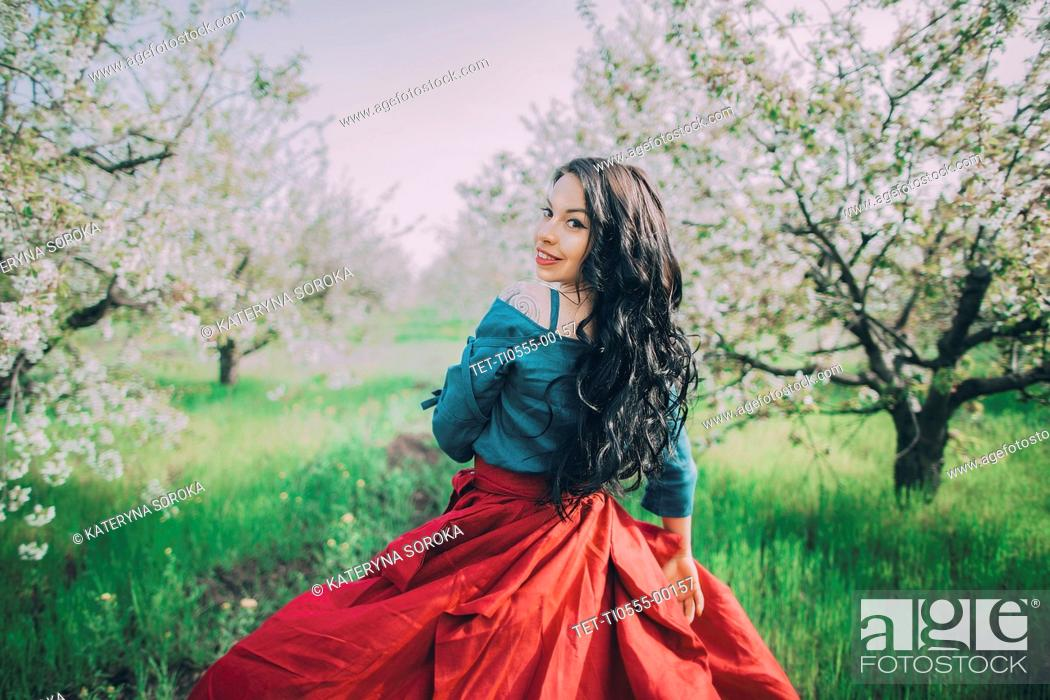 Stock Photo: Young woman in blooming orchard.