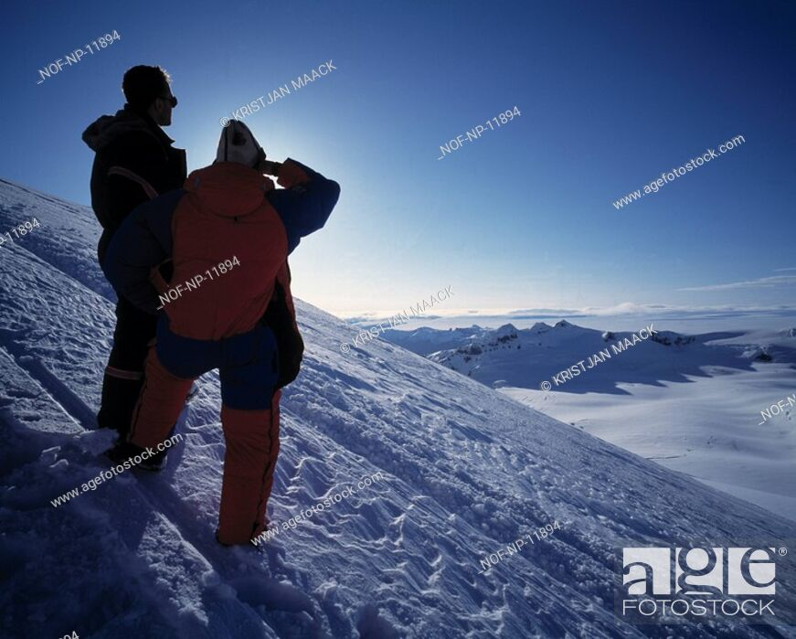 Stock Photo: A couple standing on a snow-covered Hill, enjoying the Sunset.