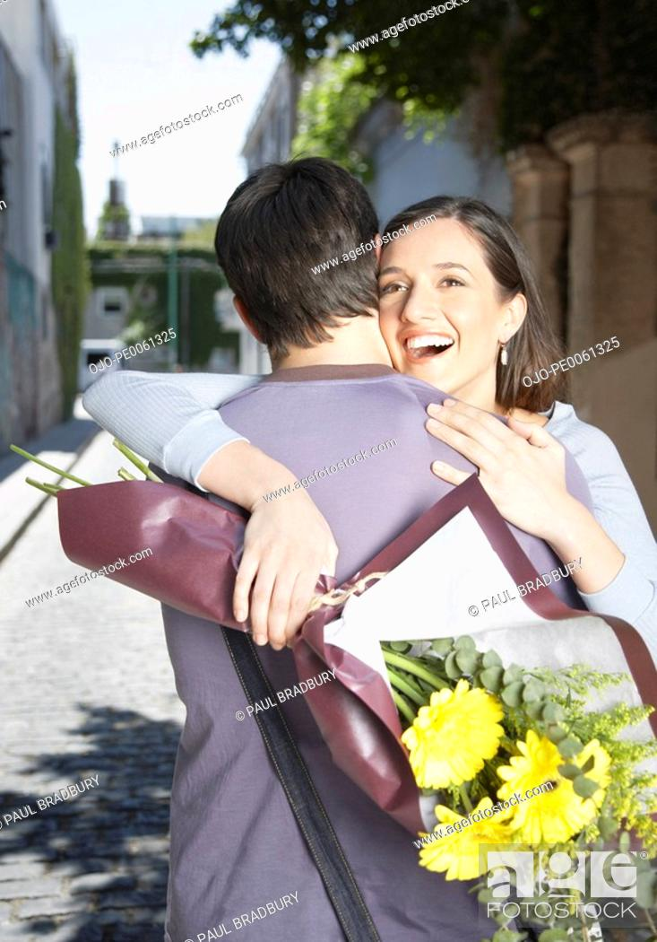 Stock Photo: Couple embracing outdoors with flowers smiling.