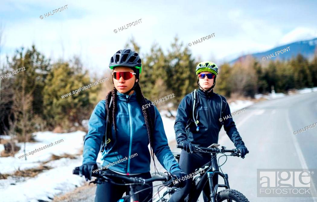 Imagen: Two mountain bikers resting on road outdoors in winter, looking at camera.