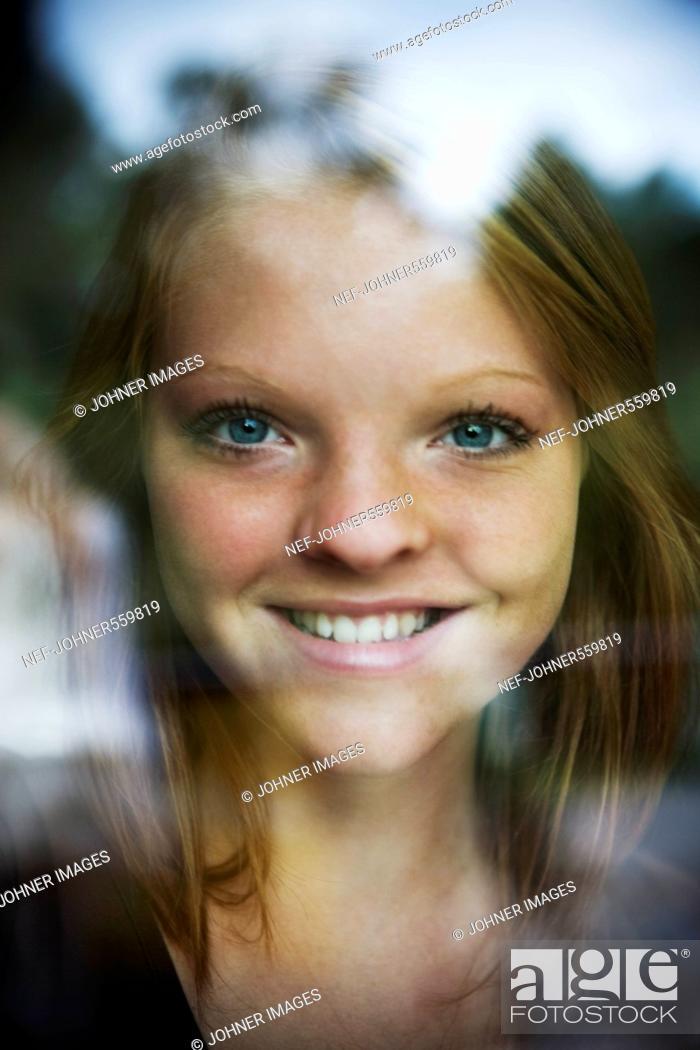 Stock Photo: A girl looking through a window, Sweden.