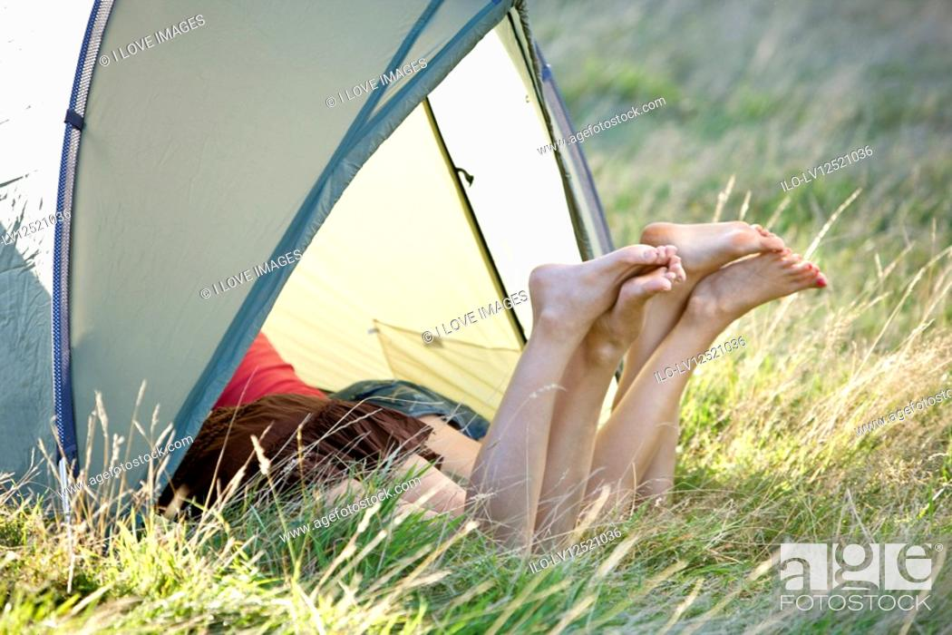 Stock Photo: Two young women with their legs sticking out of a tent.