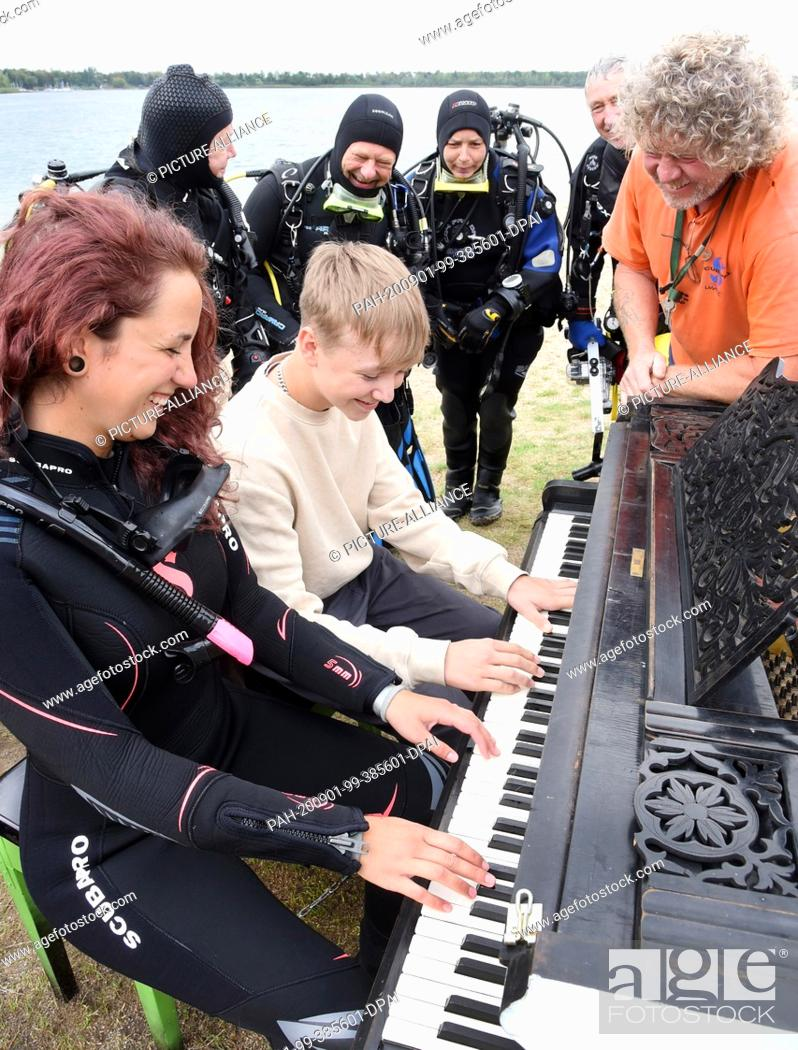 Stock Photo: 31 August 2020, Saxony, Leipzig: On the beach of the Kulkwitzer See in front of the diving school Delphin, the 15-year-old pianist Florian shows his group of.
