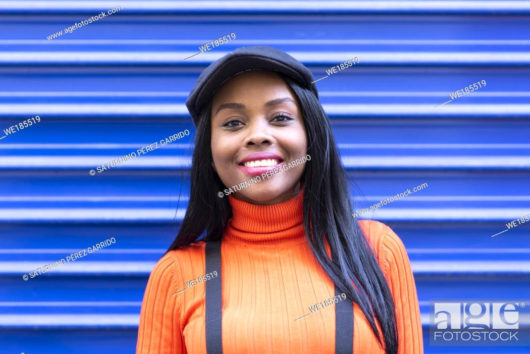 Stock Photo: Flat top of a young girl with black skin smiling on a blue background.
