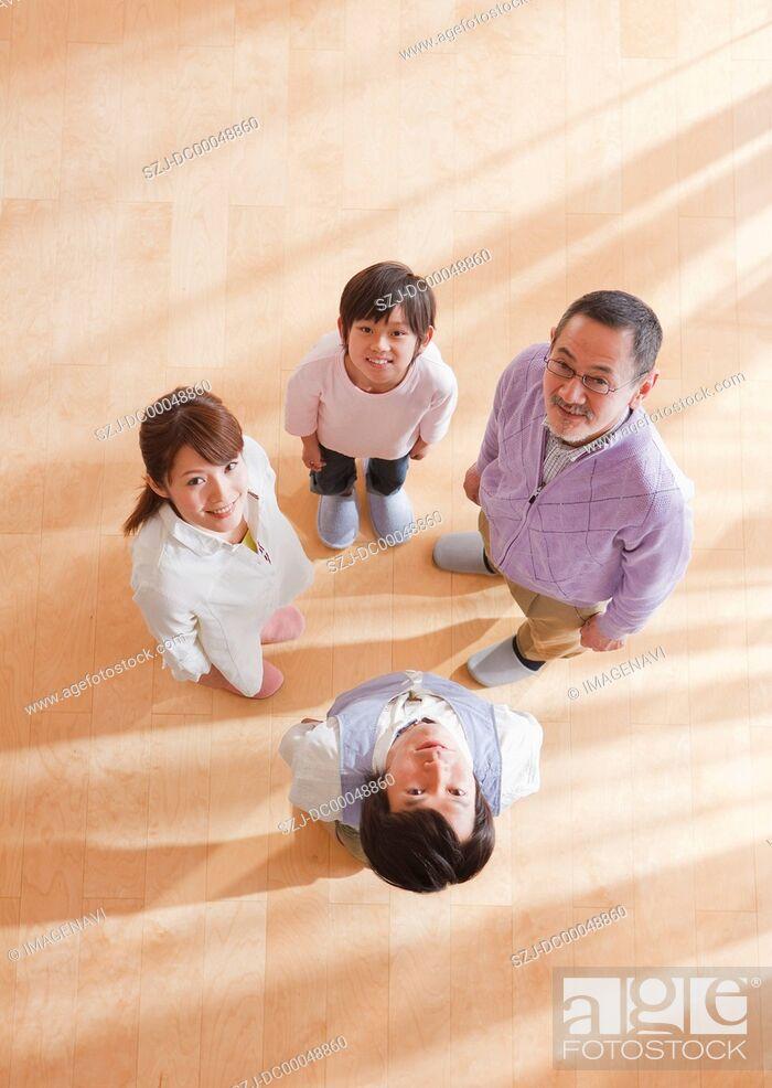 Stock Photo: Three-generation family looking up.