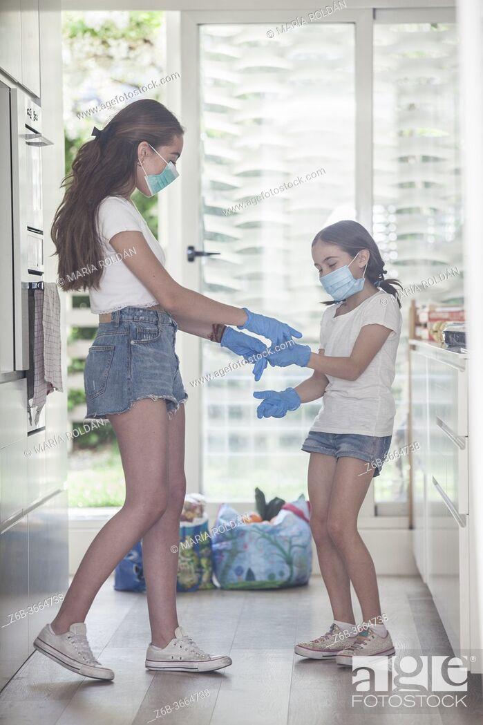 Photo de stock: sisters taking off gloves, still wearing masks.