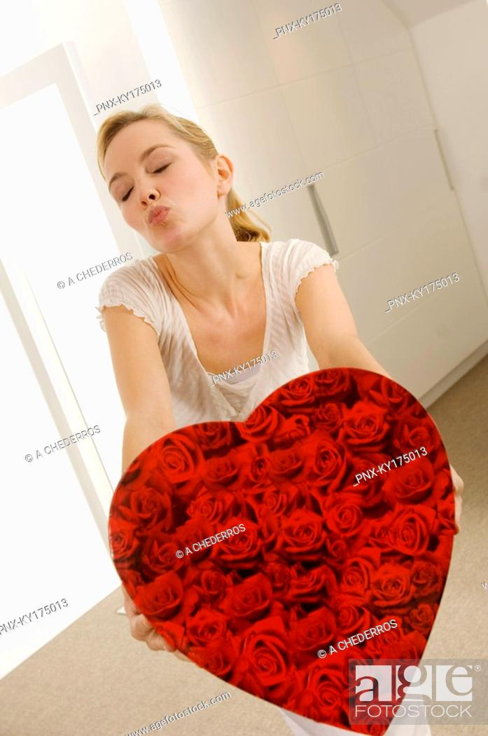 Stock Photo: Young woman holding a heart shape gift and puckering her lips.