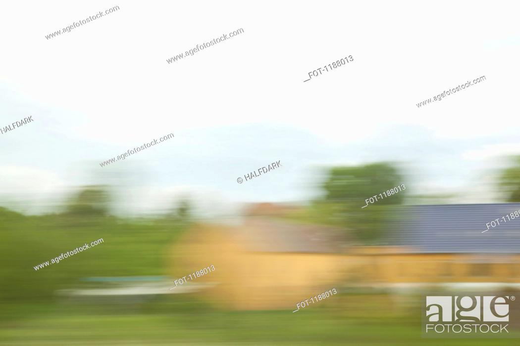 Stock Photo: Buildings and landscape in blurred motion viewed from a moving train.