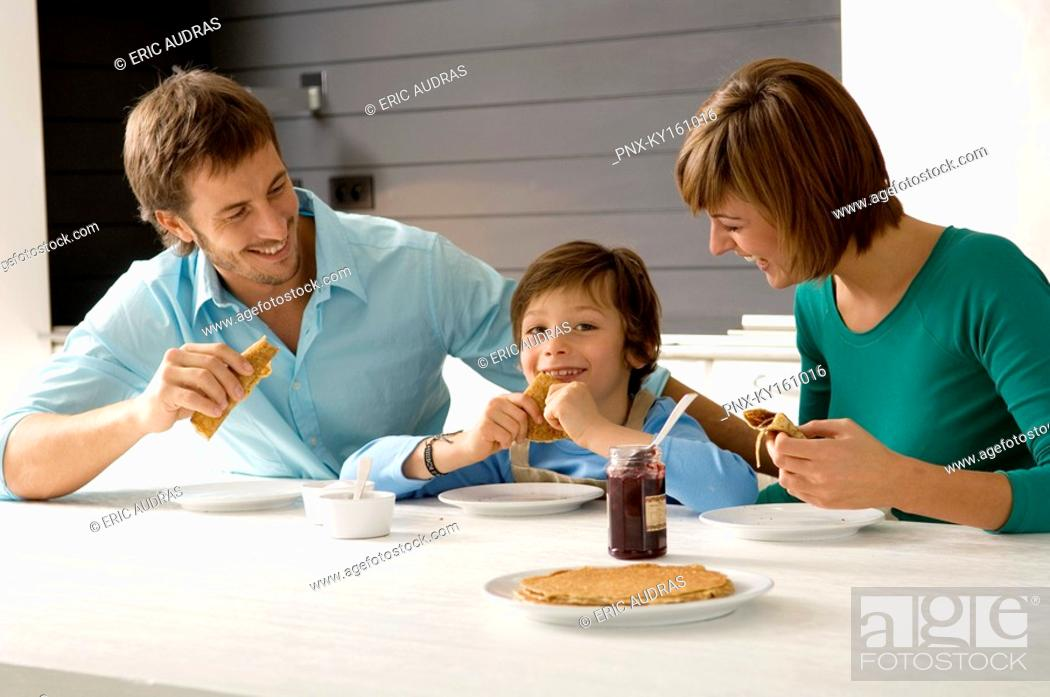 Stock Photo: Mid adult man and a young woman having breakfast with their son.