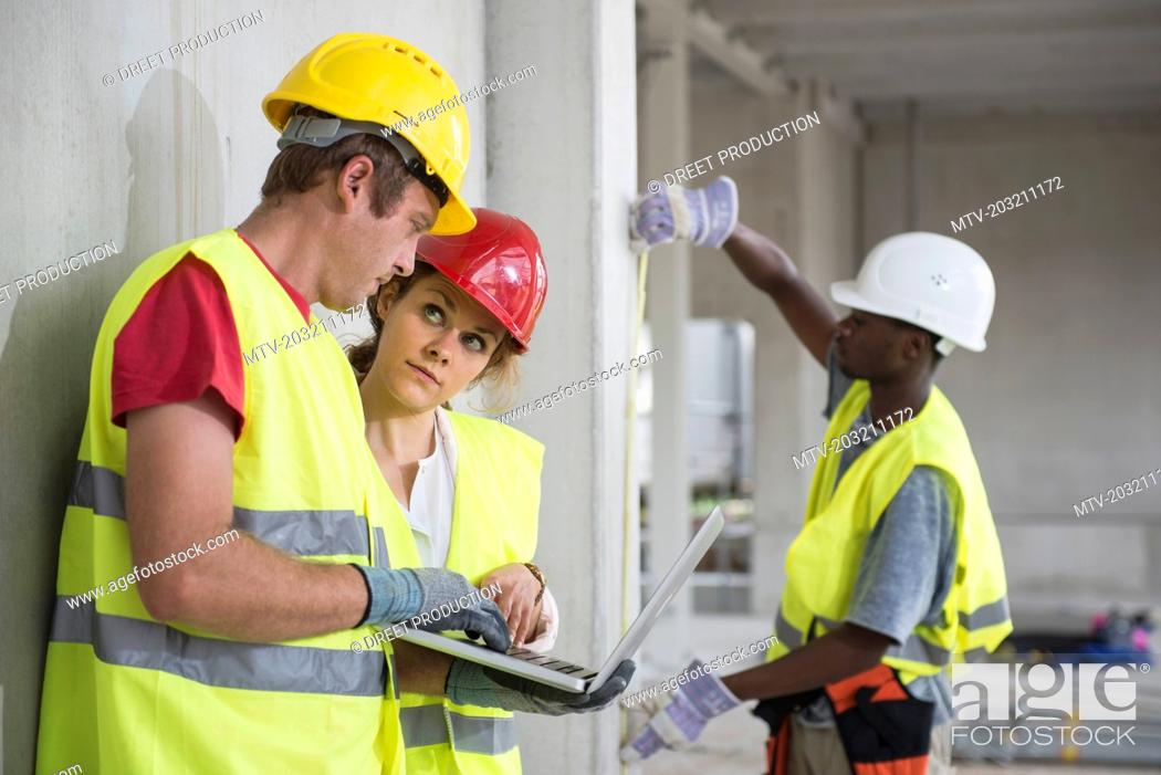 Stock Photo: Construction workers with laptop at building site.