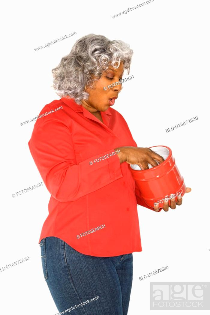 Stock Photo: Mature adult African American female with hand in jar.