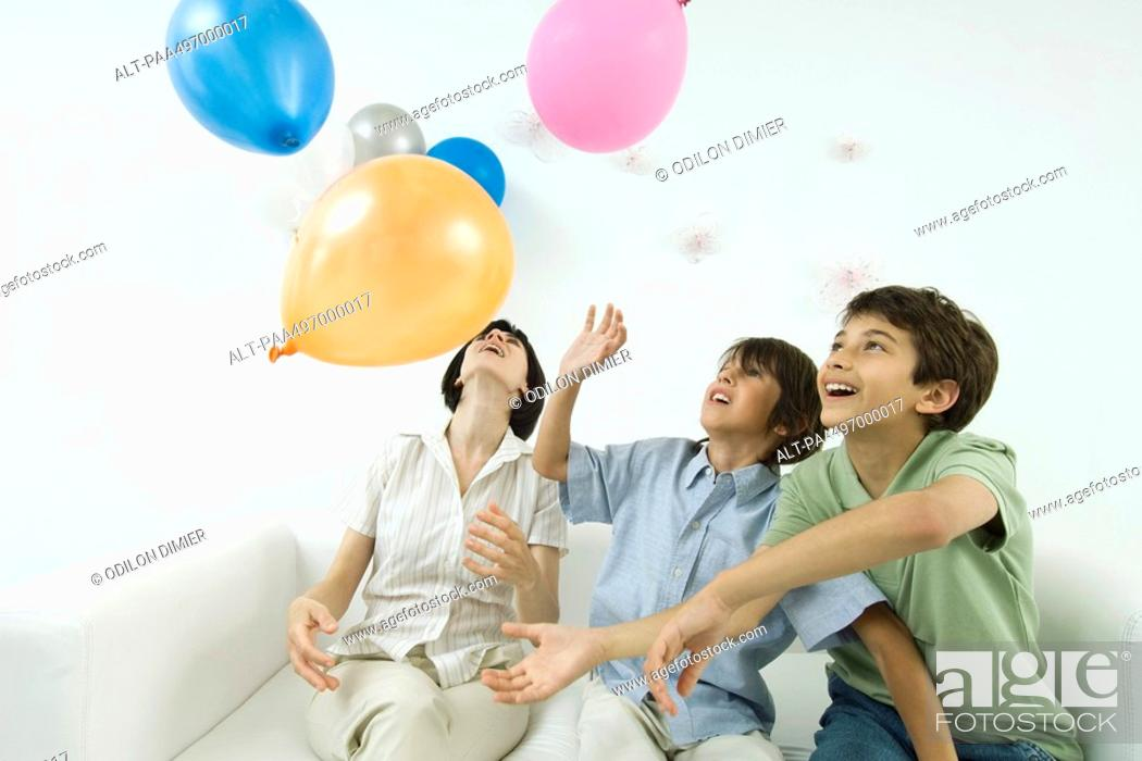 Stock Photo: Mother and two sons playing with balloons, looking up.