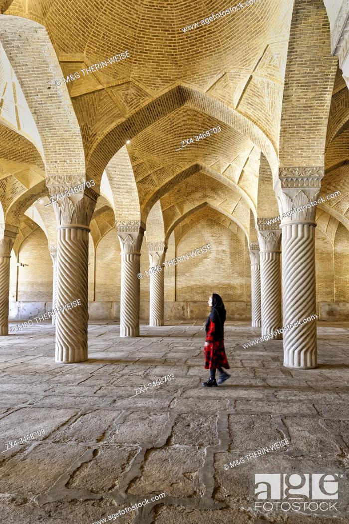 Stock Photo: Iranian woman walking through the prayer hall with Shabestan pillars, Vakil Mosque, Shiraz, Fars Province, Iran.