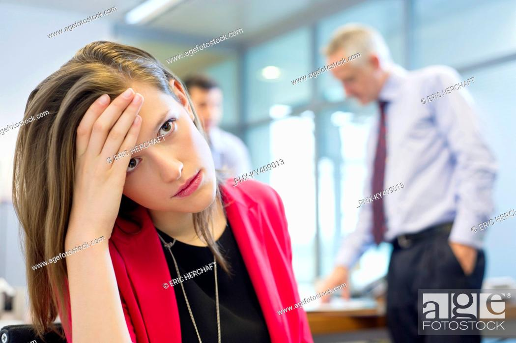 Stock Photo: Female executive looking sad in an office with her colleagues discussing in the background.