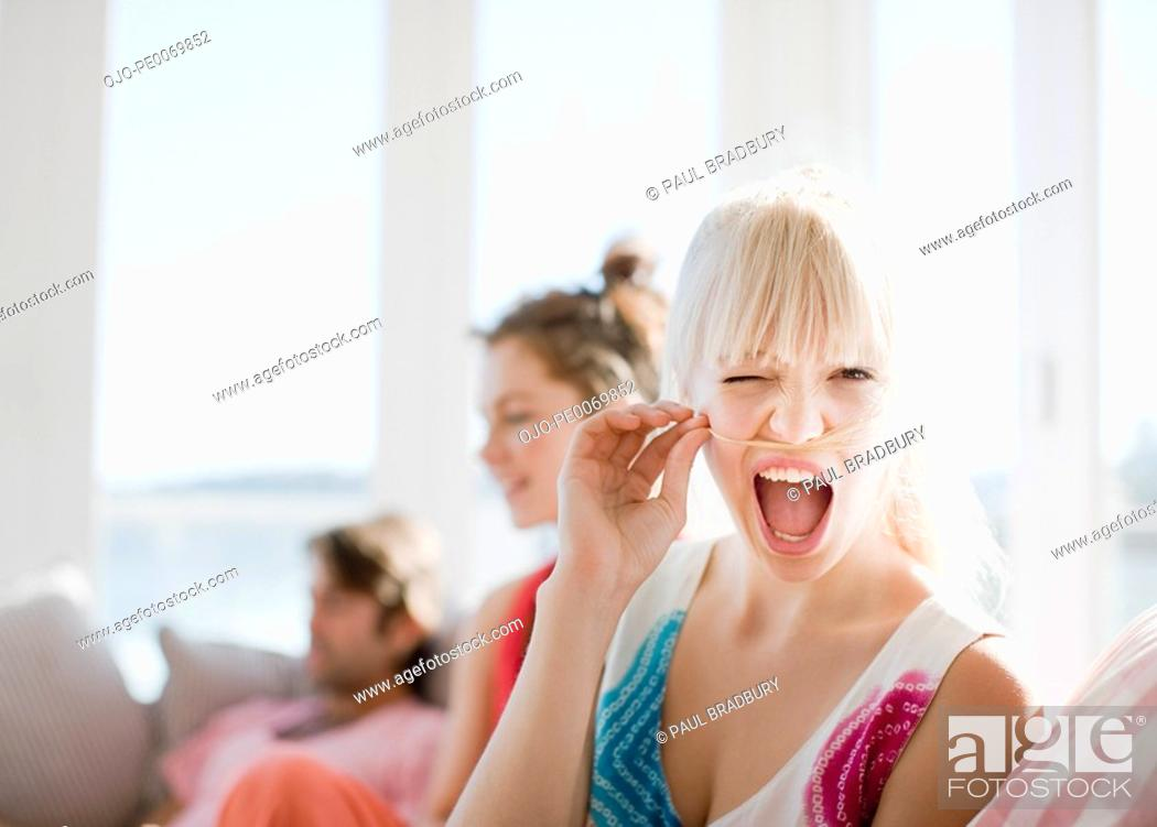 Stock Photo: Woman making face and holding hair above lip.