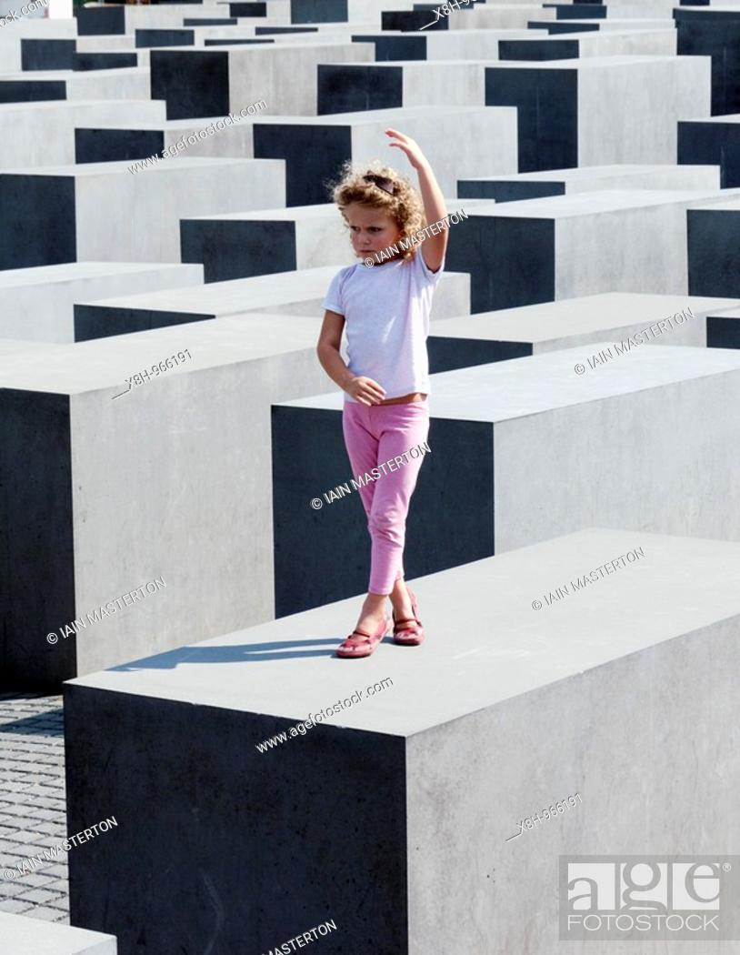 Stock Photo: young girl posing on top of concrete blocks at the Memorial to the Murdered Jews of Europe in central Berlin Germany 2008.