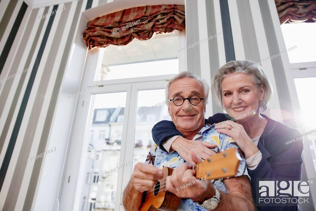 Stock Photo: Happy senior couple with man in Hawaiian shirt playing ukulele.