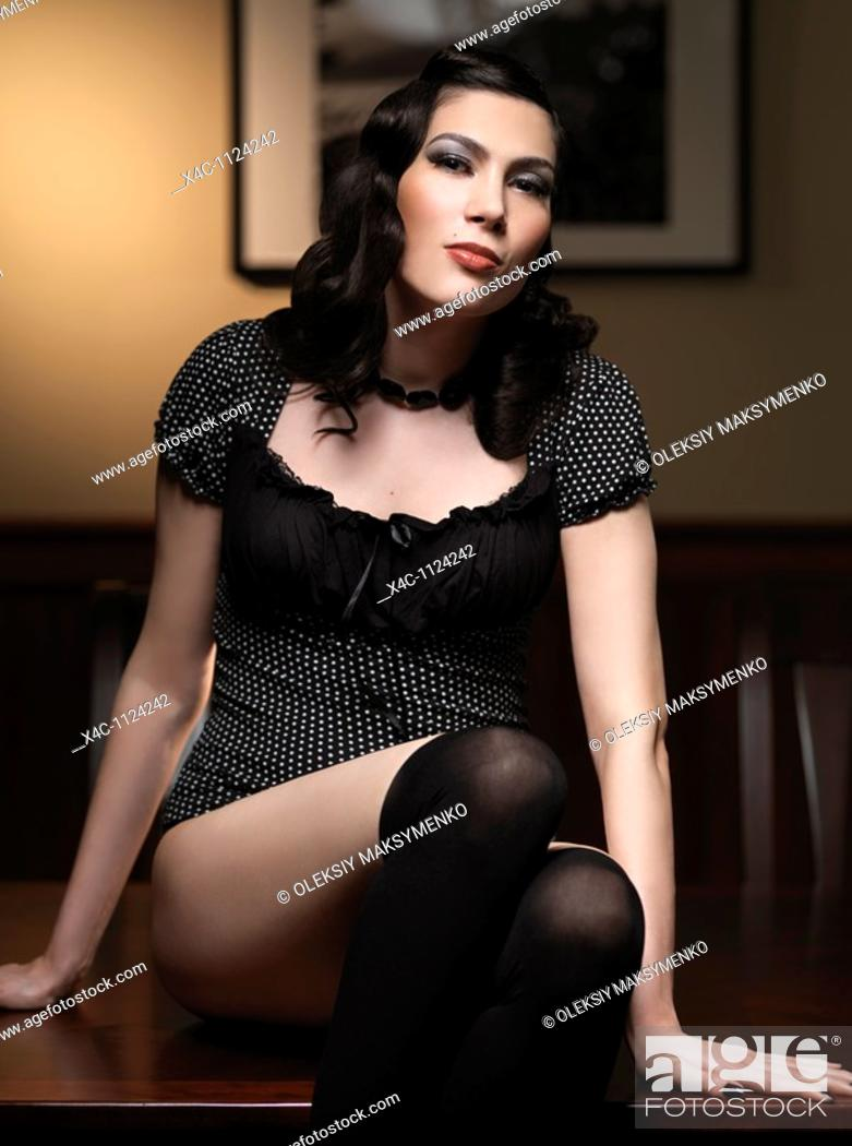 Stock Photo: Retro styled portrait of a young woman sitting on a table.