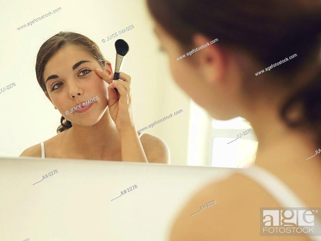 Stock Photo: Teenage girl 15-17 looking at reflection in bathroom mirror, applying make-up with brush.