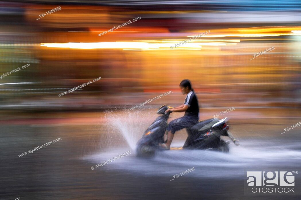 Stock Photo: Young woman rides motor scooter at speed in rain along flooded De Tham Street Pham Ngu Lao district Ho Chi Minh City Vietnam.