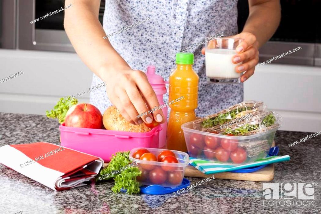 Stock Photo: Mother preparing lunch box.