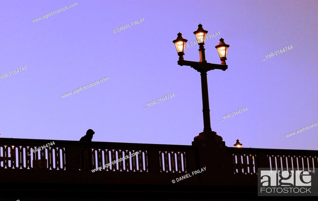 Stock Photo: Winter in London - pedestrian crossing Southwark Bridge in the heart of the city on a very cold evening after dusk.